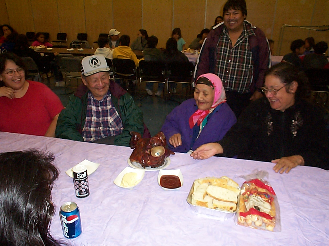 Some elders sitting at the table on the left is Kenny and his sister Susan inspecting the pigs head.